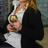 Een mooi blonde in een zwart jasje en een wit overhemd houdt een glas van brons, dat van ijzer wordt gemaakt viering stock afbeeldingen