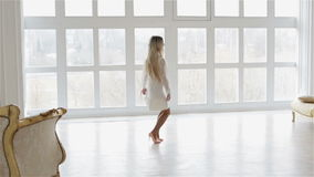 Een mooi blondemeisje bevindt zich tegen het grote venster en toont zich stock video