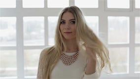 Een mooi blondemeisje bevindt zich tegen het grote venster en toont zich stock videobeelden