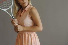 Een mooi blondemeisje met tennispalet royalty-vrije stock afbeeldingen