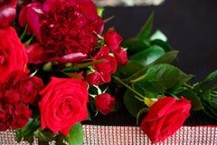 Een mooi boeket van rode rozen en pioenen is op de lijst royalty-vrije stock fotografie