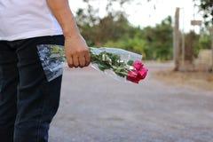Een mooi boeket van rode rozen wordt gehouden met de hand van midden oude vrouw De dag van Valentine ` s of Romaans datumconcept stock afbeeldingen