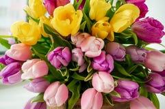 Een mooi boeket van tulpen met een witte kop voor thee Sluit omhoog stock foto's