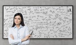 Een mooi brunette denkt over de oplossing van ingewikkeld analytisch probleem na De wiskundeformules worden neergeschreven op whi Royalty-vrije Stock Foto's