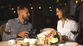 Een mooi brunette geeft een gift aan haar vriend in een restaurant op een datum stock videobeelden