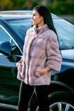Een mooi brunette in een lichte bontjas en zwarte broeken bevindt zich dichtbij een auto op een de herfst zonnige dag en lacht royalty-vrije stock foto's