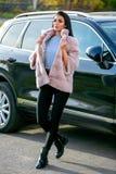 Een mooi brunette in een lichte bontjas en zwarte broeken loopt onderaan de straat naast de auto op een de herfst zonnige dag, se royalty-vrije stock fotografie