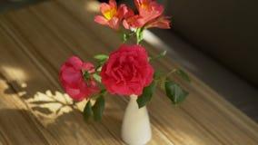Een mooi die boeket van rozen en fresia en de schaduw van het op de lijst, door zonlicht door het gordijn wordt aangestoken stock video