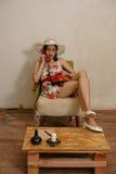 Een mooi donker-haired meisje draait een telefoonaantal Stock Foto