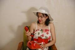 Een mooi donker-haired meisje draait een telefoonaantal Royalty-vrije Stock Afbeeldingen