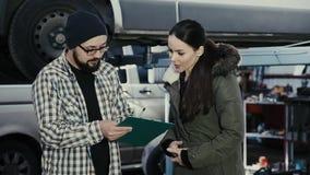 Een mooi donkerbruin meisje, een cliënt van een centrum van de autodienst, neemt een auto van een reparatie en ondertekent docume stock video