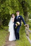 Een mooi echtpaar in huwelijk kleedt zich, stellend voor een foto schietend in een Witrussisch dorp dichtbij de omheining, met ee Royalty-vrije Stock Foto's
