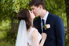 Een mooi echtpaar in huwelijk kleedt zich, stellend voor een foto schietend in een Witrussisch dorp dichtbij de omheining, met ee Royalty-vrije Stock Afbeeldingen