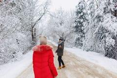 Een mooi familiepaar die op een sneeuwweg in het hout lopen stock afbeeldingen