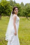 Een mooi gehuwd meisje in huwelijkskleding, die voor een foto stellen die in een Witrussisch dorp schieten Groene Achtergrond Royalty-vrije Stock Fotografie