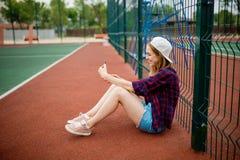 Een mooi glimlachend blond meisje die geruit overhemd, wit GLB en denimborrels dragen zittend leunt op guardlattice stock foto