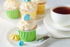 Een mooi helder damestheekransje met kop thee cupcake met schuimgebakjes stock afbeeldingen