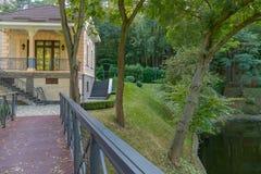 Een mooi huis met een trap en een voetgangersbrug die naar het gaan gevestigd op de kust van een meer met groen gras en stock foto's