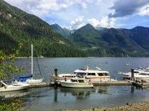 Een mooi jachthavenhoogtepunt van boten en omringd door bossen en bergen in een verre inham in Indisch Wapen, buiten Vancouver stock afbeeldingen
