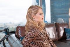 Een mooi jong blondemeisje in een modieuze kleding met een onbekwaamheid, die op een leerbank tegen de achtergrond stellen royalty-vrije stock foto