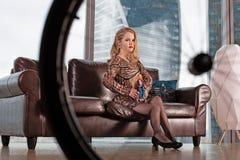 Een mooi jong blondemeisje in een modieuze kleding met een onbekwaamheid, die op een leerbank tegen de achtergrond stellen royalty-vrije stock afbeelding