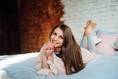 Een mooi jong brunette in een licht overhemd lacht terwijl het liggen in bed in haar moderne slaapkamer Leuk meisje die thuis rus Stock Fotografie