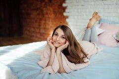 Een mooi jong brunette in een licht overhemd lacht terwijl het liggen in bed in haar moderne slaapkamer Leuk meisje die thuis rus Stock Foto's