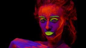 Een mooi jong half-naked meisje die met gloeiende verf op haar lichaam in zwart licht dansen Mooie vrouw met het gloeien stock footage