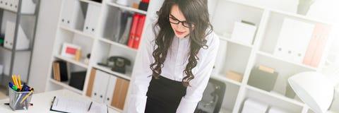 Een mooi jong meisje bevindt zich neiging over een bureau, houdt een pen in haar hand en bekijkt de agenda stock afbeeldingen