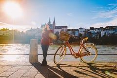 Een mooi jong meisje bevindt zich op de dijk dichtbij een stadsfiets met een mand rood in Zwitserland, de stad van Bazel zonnig stock afbeelding