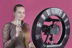 Een mooi jong meisje blogger heeft het stellen op de camera met tandenborstels in haar hand stock afbeeldingen