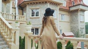 Een mooi jong meisje draagt modieuze kleren, een modieuze hoed en een laag, tribunes buiten een groot steengebouw, gangen stock video