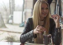 Een mooi jong meisje drinkt thee in een restaurant en geniet van het royalty-vrije stock foto