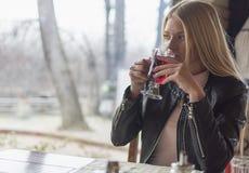 Een mooi jong meisje drinkt thee in een restaurant en geniet van het royalty-vrije stock afbeeldingen