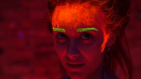 Een mooi jong meisje met gloeiende verf op haar gezicht en haar in het zwarte lichte spreken Mooie vrouw met het gloeien stock video
