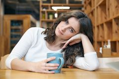 Een mooi jong meisje met lang haar en expressieve ogen leunde over aan de lijst houdend een mok koffie royalty-vrije stock afbeelding