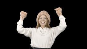 Een mooi jong meisje met lang rood haar in een gebreide hoed en vuisthandschoenen drukt de emoties van overwinning uit golvend ha stock footage