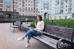 Een mooi jong meisje met lange bruine haarzitting op een bank met een boek, holdingsoogglazen Zij verliet het huis op een warme e royalty-vrije stock afbeeldingen