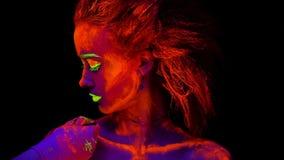 Een mooi jong meisje met ultraviolette verf op haar lichaam die een hand die van een kunstenaar met een borstel bekijken, haar sc stock videobeelden