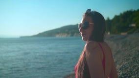 Een mooi jong meisje in een rood zwempak uit één stuk en glazen zit op de kust stock footage
