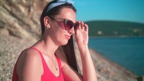 Een mooi jong meisje in een rood zwempak uit één stuk en glazen zit op de kust stock videobeelden
