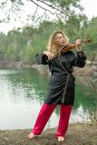 Een mooi jong meisje speelt de viool op de kust van het meer Royalty-vrije Stock Afbeeldingen