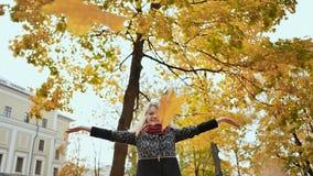 Een mooi jong meisje werpt gelukkig op een armvol de herfstbladeren Het seizoen van de herfst in het stadspark Plezier in de herf stock videobeelden