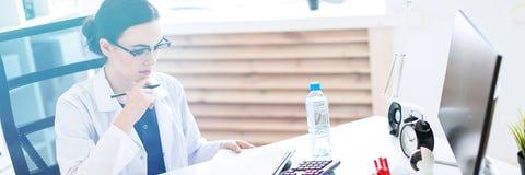 Een mooi jong meisje in een witte robe zit bij een computerbureau met documenten en een pen in haar handen royalty-vrije stock fotografie