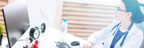 Een mooi jong meisje in een witte robe zit bij een computerbureau met documenten en een pen in haar handen stock foto