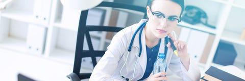 Een mooi jong meisje in een witte robe zit bij het computer bureau, het houden van een open fles water en het lopen stock foto's