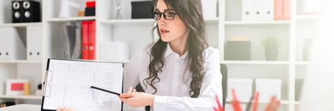 Een mooi jong meisje zit bij een lijst in het bureau en richt een potlood op de informatie in het document royalty-vrije stock foto's