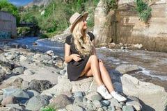 Een mooi jong vrouwenblonde met lang haar in een hoedenzitting op een rotsachtige kust door de rivier Rond de bergen stock afbeeldingen