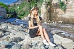 Een mooi jong vrouwenblonde met lang haar in een hoedenzitting op een rotsachtige kust door de rivier Rond de bergen royalty-vrije stock fotografie