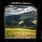 Een mooi Karpatisch landschap door een boog van een venster Stock Afbeeldingen